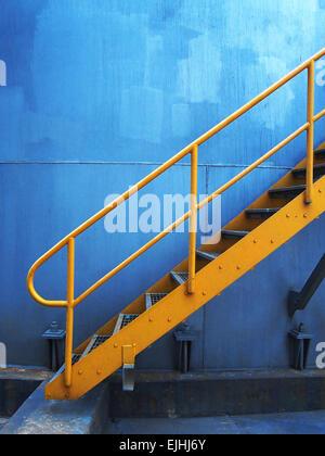 Yellow iron stairs on the bluish background - Stock Photo