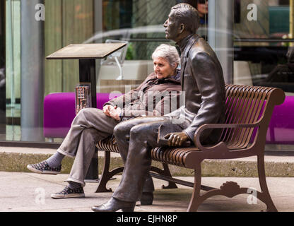 Woman sitting on bench next to bronze statue of a man, New York City, USA - Stock Photo
