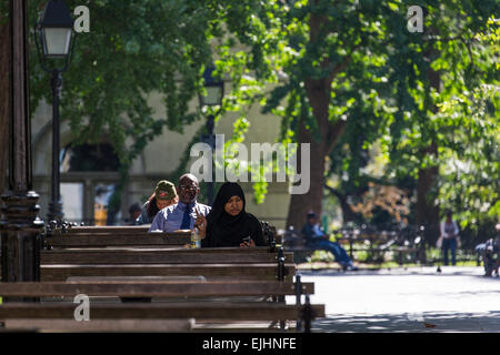 People sitting on benches in park in Manhattan, New York City, USA - Stock Photo