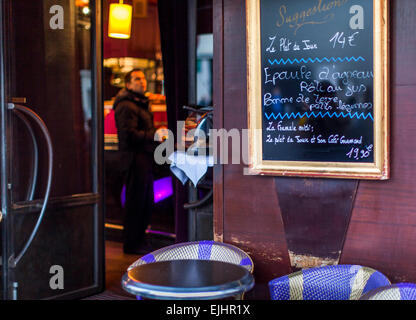 Cafe restaurant in Paris, France with chalkboard menu and outside table and chairs - Stock Photo