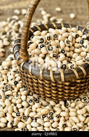 A small wicker basket full of dried black eye peas. - Stock Photo