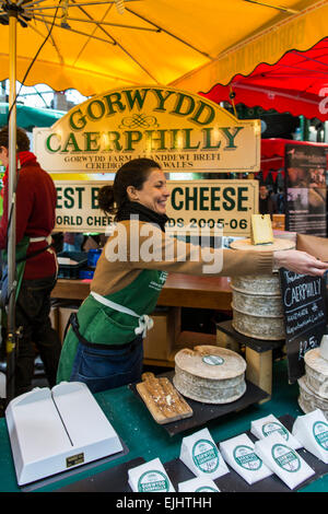 Woman at Caerphilly cheese stand at Borough Market, London, England - Stock Photo