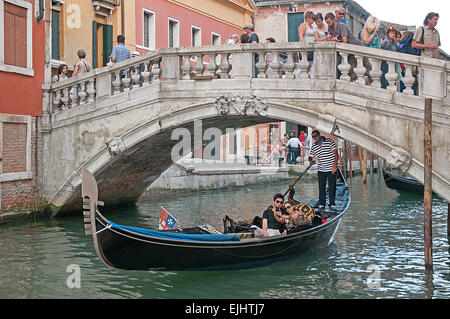 Young Japanes couple taking a selfie photograph on gondola on Rio de Palazzo de Canonica Venice Italy near Bridge - Stock Photo
