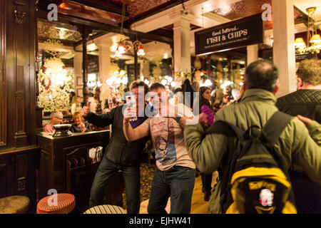 Two men posing and laughing inside the Salisbury pub, London, England - Stock Photo