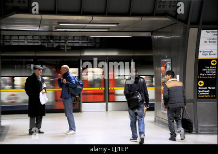 London England UK - Commuters about to board a tube at London Bridge underground station on Jubilee Line - Stock Photo