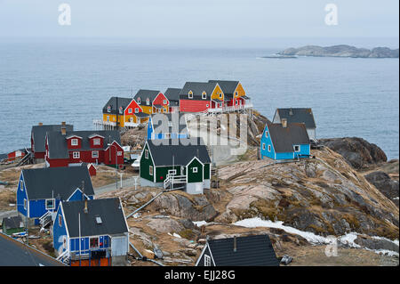 SISIMIUT, QEQQATA / GREENLAND - JUNE 12:  Colorful houses perched on rocks in Sisimiut, Greenland on JUNE 12th, - Stock Photo