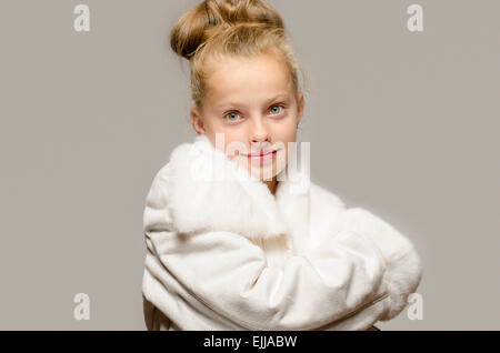 Girl wearing a white long coat and looking like snow white, beautiful kid worming up in for the winter time - Stock Photo