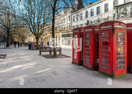 Traditional red telephone boxes on the Promenade in Cheltenham, Gloucestershire - Stock Photo