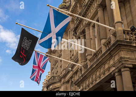 The Scottish Saltire, Union Jack  and the flag of Rocco Forte Hotels fly outside the Balmoral Hotel on Princes Street, - Stock Photo