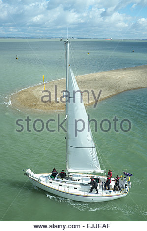 A yacht named 'Janthina ' leaves Cowes on the Isle of Wight, and heads out in to The Solent. UK. - Stock Photo
