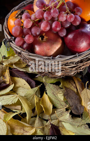 Old basket fruit bowl with autumn fruits isolated over black background. Surface full of dry leaves - Stock Photo