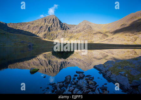 Carrauntoohil and Beenkeragh reflected in Lough Callee, Hag's Glen, MacGillycuddy's Reeks, County Kerry, Ireland. - Stock Photo