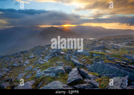 Sunset over Caher, Ireland's third highest mountain, from Carrauntoohil, MacGillycuddy's Reeks, County Kerry, Ireland. - Stock Photo