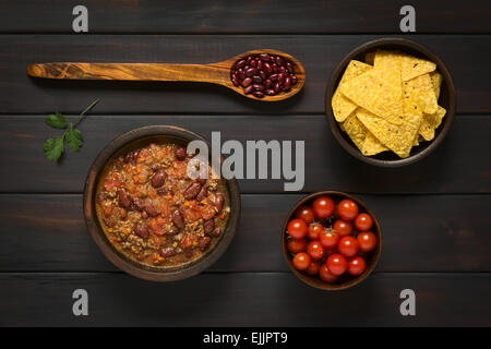 Overhead shot of chili con carne and tortilla chips with ingredients dried kidney beans and cherry tomatoes - Stock Photo