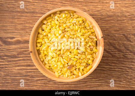 Cereal bulgur in a wooden bowl closeup view from above - Stock Photo