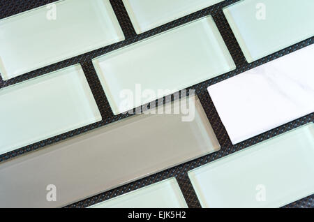 green white and taupe colored glass and porcelain subway tile or backsplash against black background arranged in - Stock Photo