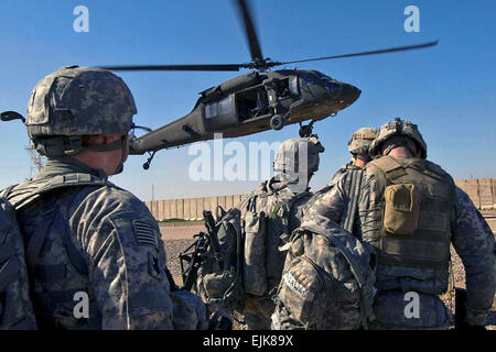 U.S. Army soldiers prepare to board a UH-60 Black Hawk helicopter landing to pick them up and transport them to - Stock Photo