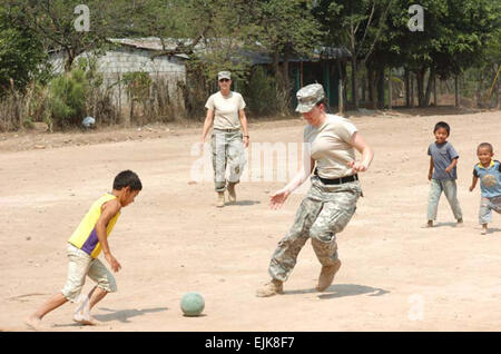 U.S. Army Spc. Teri McMurray, a medic with the 4005th Army Hospital, plays soccer with local children at a school - Stock Photo