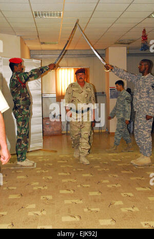 An Iraqi soldier walks under crossed sabers as he is recognized as a new noncommissioned officer during a combined - Stock Photo