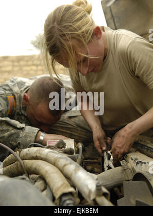 U.S. Army Sgt. Michael Holeman and Spc. Amy Rodgers perform maintenance on a vehicle at a patrol base in As Sadah, - Stock Photo