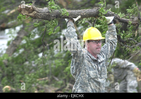 Kansas National Guard Sgt. Frankie Schubert clears a tree in front of the courthouse of Greensburg, Kan., on May - Stock Photo