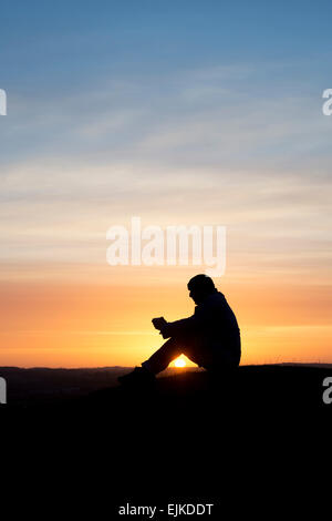 Thoughtful man sitting on a hillside at sunrise. Silhouette - Stock Photo