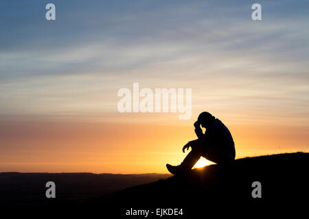 Worried man sitting on a hillside at sunrise. Silhouette - Stock Photo