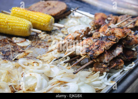 Barbecued chicken kebabs on skewers, corn on the cob and onions - Stock Photo