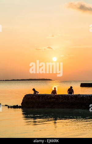 People paddling in the sea at sunset on the island of Makunudu in the Maldives - Stock Photo