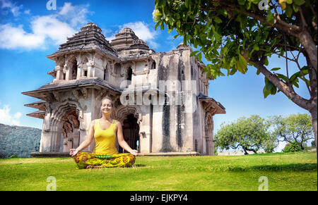 Woman doing yoga near Lotus Mahal in royal center at blue sky in Hampi, Karnataka, India - Stock Photo