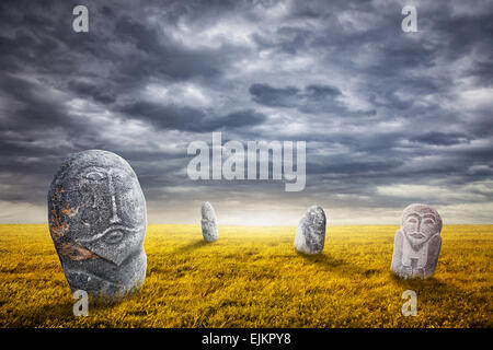 Ancient balbal statues on the field at overcast sky in central Asia - Stock Photo