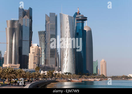 Pedestrians walk the waterfront corniche, below skyscrapers, in the city of Doha in the gulf state of Qatar. - Stock Photo
