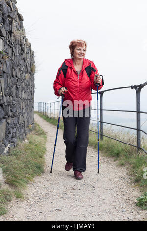 Active senior woman Nordic walking on rocky trail outdoors. - Stock Photo
