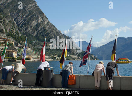 Tourists at Limone,Lake Garda, Italy, bending over a wall to view the lake, with flags of European countries on - Stock Photo