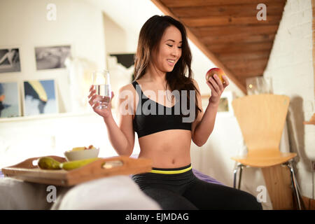 Healthy lifestyle: A happy smiling slim fit attractive young  asian ethnic chinese girl woman relaxing drinking - Stock Photo