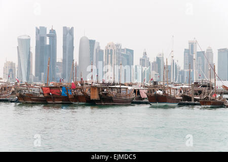 A fleet of dhow boat docked in a port, with the skyline of Doha, Qatar, in the background. - Stock Photo