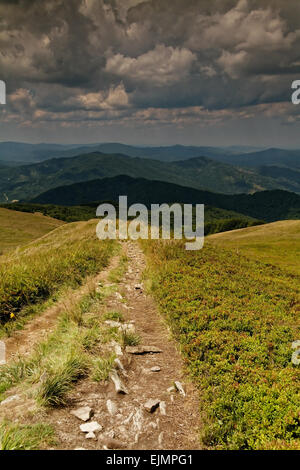 Poland.Bieszczady mountins in summer.Tourist trail in the mountains.Many clouds on the sky.In the sky one can see - Stock Photo