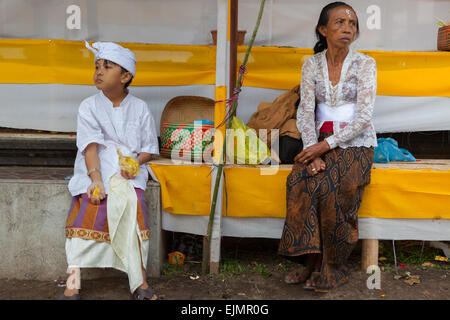 Young boy and old woman wait for a religious ceremony in Besakih area, Bali, Indonesia. - Stock Photo