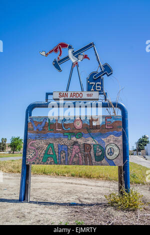 The welcome to San Ardo sign featuring a sculpture of a oil drilling pumpjack with a cowboy with spurs on riding - Stock Photo
