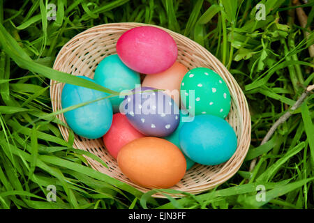 Easter eggs basket in the green grass from above - Stock Photo