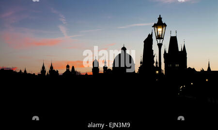 Night view of Charles Bridge before dawn with silhouettes of the buildings and sky lighting up - Stock Photo