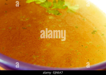 Homemade meat stock with herbs in a bowl close up - Stock Photo