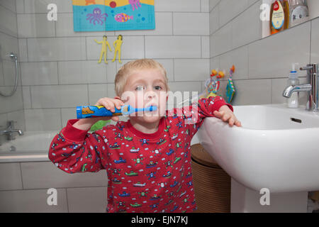 Four year old boy brushing his teeth with an electric toothbrush in the bathroom before bedtime, UK - Stock Photo
