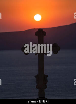 Silhouette of a Greek Orthodox cross on a church top against the evening sunset, Santorini (Thera), Greece. - Stock Photo