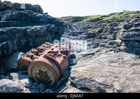 The engine of a boat lies rusting on a rocky shore. - Stock Photo