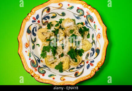 Stuffed cheese tortelloni with onions, parsley and Parmesan cheese in a ornate Italian pasta bowl - Stock Photo
