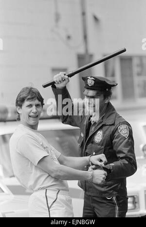 1986 World Cup Finals in Mexico. England footballer Gary Lineker holds his hands out to be handcuffed by a policeman - Stock Photo