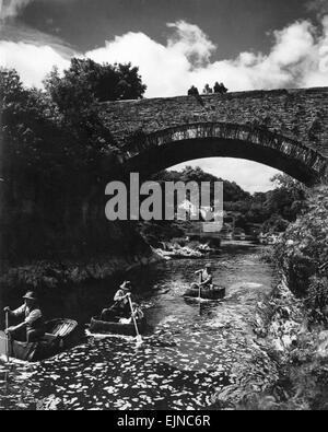Passers-by stop on Cenarth Bridge to look at the coracle men plying their craft down the Teifi. Following a pattern - Stock Photo