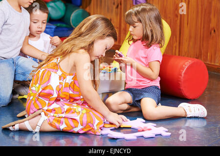 Children playing together in preschool with a big jigsaw puzzle - Stock Photo
