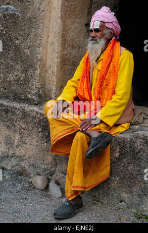Indian Vishnu devotee Sadhu Holy man sitting on a wall at Royal cenotaphs Orchha Madhya Pradesh India - Stock Photo
